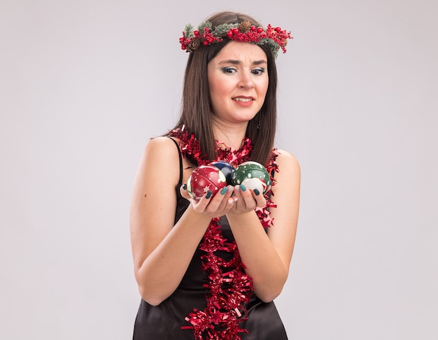 Verärgertes junges hübsches kaukasisches mädchen, das weihnachtskopfkranz und lamettagirlande um den hals trägt und weihnachtskugeln einzeln auf weißem hintergrund mit kopienraum betrachtet und betrachtet