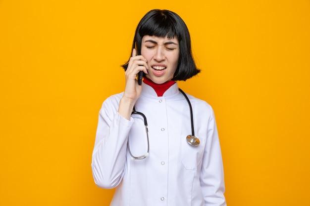 Verärgertes junges hübsches kaukasisches mädchen in arztuniform mit stethoskop, das am telefon spricht