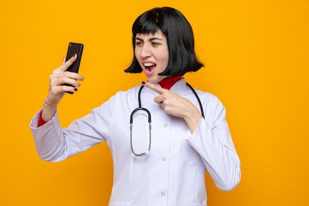 Verärgertes junges hübsches kaukasisches mädchen in arztuniform mit stethoskop, das auf telefon hält und zeigt