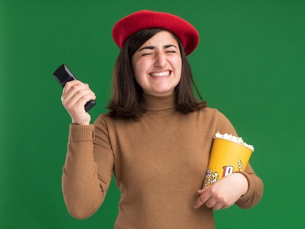 Verärgertes junges hübsches kaukasisches mädchen mit baskenmütze, das tv-controller und popcorn-eimer hält, isoliert auf grüner wand mit kopierraum