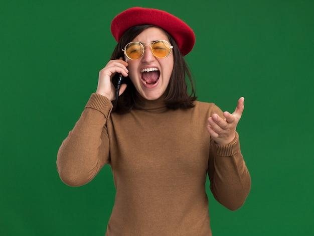 Verärgertes junges hübsches kaukasisches mädchen mit baskenmützenhut in der sonnenbrille, die jemanden am telefon auf grün anschreit