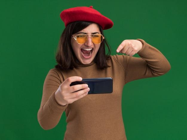 Verärgertes junges hübsches kaukasisches mädchen mit baskenmützenhut in der sonnenbrille, die telefon auf grün hält und zeigt