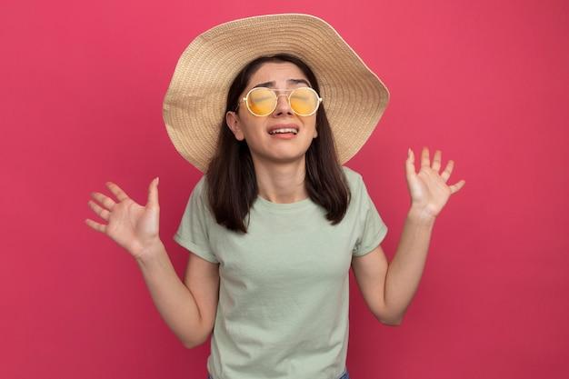 Verärgertes junges hübsches kaukasisches mädchen mit strandhut und sonnenbrille, das leere hände mit geschlossenen augen zeigt
