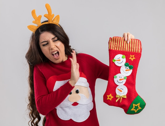 Verärgertes junges hübsches mädchen mit rentiergeweih-stirnband und weihnachtsmann-pullover, das weihnachtsstrumpf hält und betrachtet, die ablehnungsgeste einzeln auf weißer wand macht