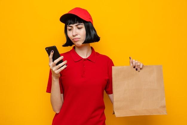 Verärgertes junges kaukasisches liefermädchen, das lebensmittelverpackungen aus papier hält und auf das telefon schaut