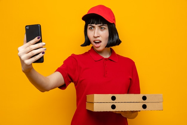Verärgertes junges kaukasisches liefermädchen, das pizzakartons hält und jemanden anschreit, der auf das telefon schaut