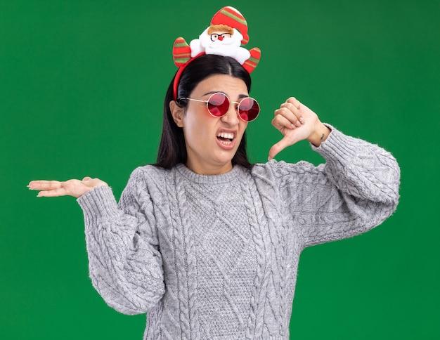 Verärgertes junges kaukasisches mädchen, das weihnachtsmann-stirnband mit brille trägt, die kamera betrachtet, die leere hand und daumen unten auf grünem hintergrund zeigt