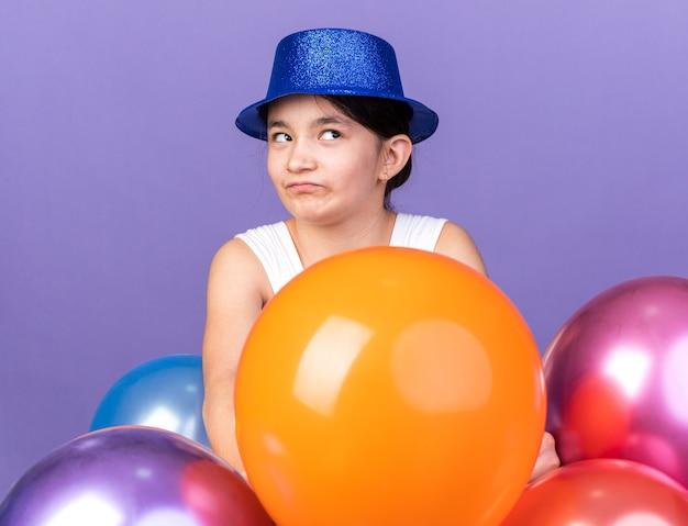 Verärgertes junges kaukasisches mädchen mit blauem partyhut, der mit heliumballons steht und seitlich isoliert auf lila wand mit kopierraum schaut