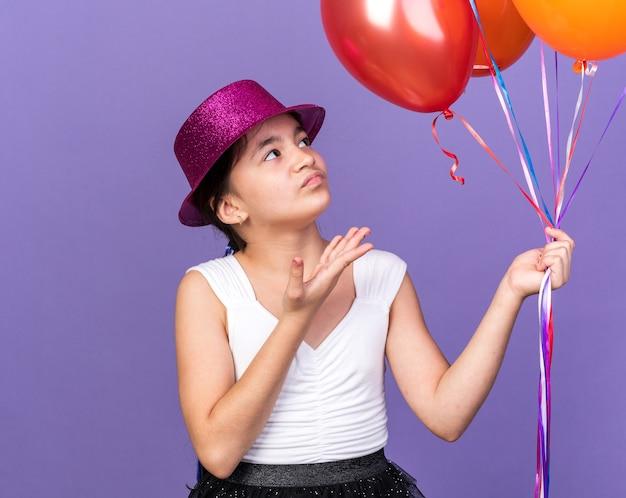 Verärgertes junges kaukasisches mädchen mit violettem partyhut, das heliumballons hält und auf lila wand mit kopienraum zeigt