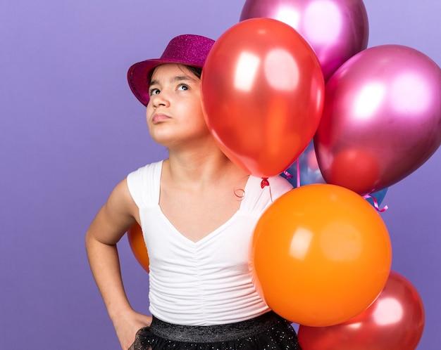 Verärgertes junges kaukasisches mädchen mit violettem partyhut, der heliumballons hält und isoliert auf lila wand mit kopienraum nach oben schaut