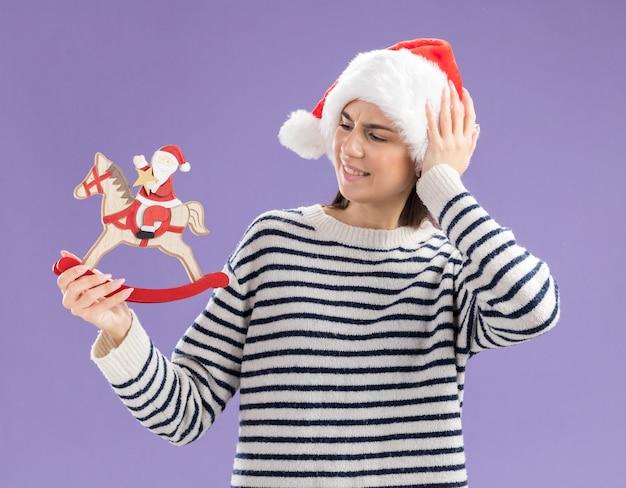 Verärgertes junges kaukasisches mädchen mit weihnachtsmütze legt die hand auf den kopf und sieht den weihnachtsmann auf schaukelpferddekoration einzeln auf lila wand mit kopienraum an