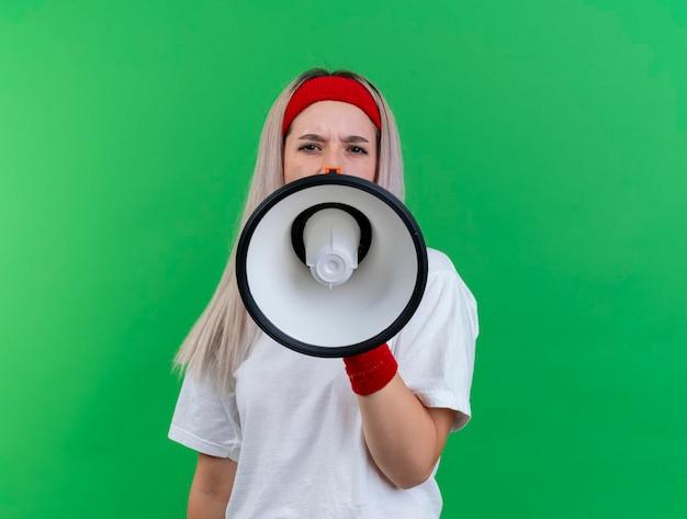 Verärgertes junges kaukasisches sportliches mädchen mit zahnspangen, die stirnband tragen