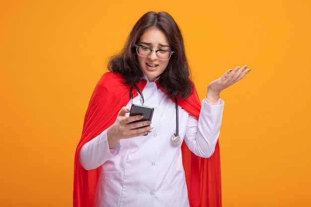 Verärgertes junges kaukasisches superheldenmädchen, das arztuniform und stethoskop mit brille trägt und auf das handy schaut, das leere hand isoliert an der wand zeigt