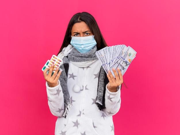 Verärgertes junges krankes mädchen, das medizinische maske mit schal hält, der pillen mit bargeld lokalisiert auf rosa hält