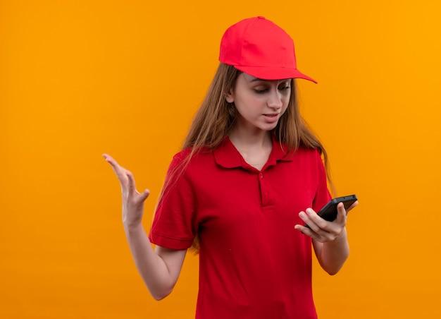 Verärgertes junges liefermädchen in der roten uniform, die handy hält, das es auf lokalisiertem orange raum betrachtet