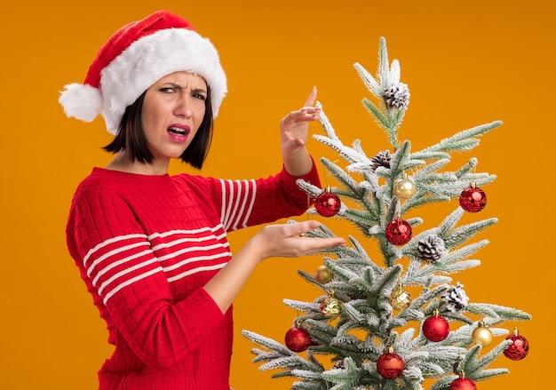 Verärgertes junges mädchen, das weihnachtsmütze trägt, die in der profilansicht nahe dekoriertem weihnachtsbaum zeigt, der auf kamera schaut, die auf orange hintergrund lokalisiert wird