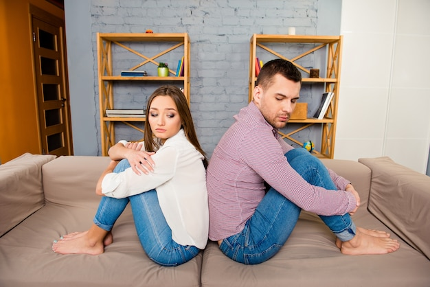Verärgertes junges paar, das rücken an rücken sitzt