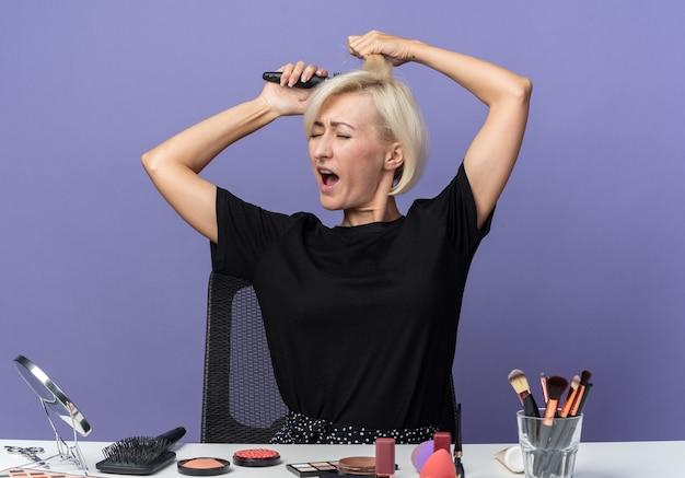 Verärgertes junges schönes mädchen sitzt am tisch mit make-up-werkzeugen, die haare einzeln auf blauer wand kämmen