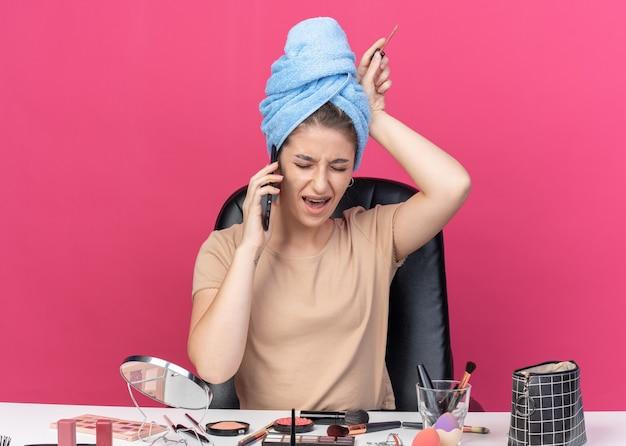 Verärgertes junges schönes mädchen sitzt am tisch mit make-up-werkzeugen, die haare in handtuch halten und lipgloss halten, spricht am telefon isoliert auf rosa wand pink