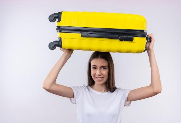 Verärgertes junges schönes reisendes mädchen, das koffer auf schulter hält und kamera mit genervtem ausdruck betrachtet