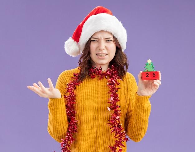 Verärgertes junges slawisches mädchen mit weihnachtsmütze und mit girlande um hals, der weihnachtsbaumverzierung hält und seite lokalisiert auf lila hintergrund mit kopienraum betrachtet