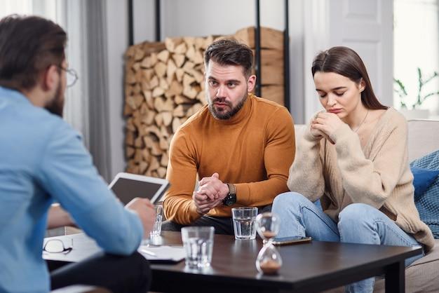 Verärgertes kaukasisches paar von mann und frau, die gespräch mit psychologe auf therapiesitzung im hellen raum haben.