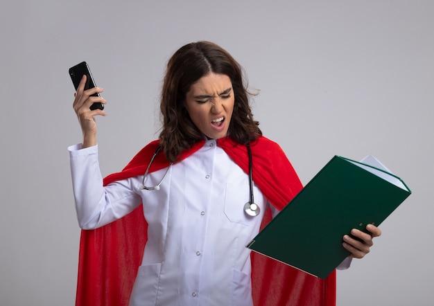Verärgertes kaukasisches superheldenmädchen in arztuniform mit rotem umhang und stethoskop hält aktenordner