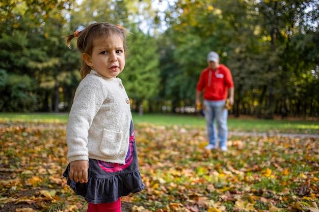 Verärgertes kind im park mit papa wütendes mädchen im park sieht den kameravater an und