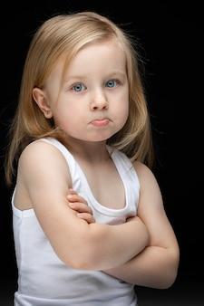Verärgertes kind in einem weißen unterhemd, das auf schwarz steht