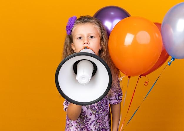 Verärgertes kleines blondes mädchen, das heliumballons hält und in den lautsprecher schreit, der auf orangefarbener wand mit kopierraum isoliert ist?