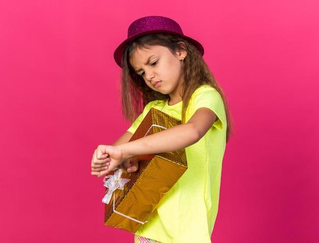 Verärgertes kleines kaukasisches mädchen mit lila partyhut, das geschenkbox hält und ihre hand einzeln auf rosa wand mit kopienraum betrachtet