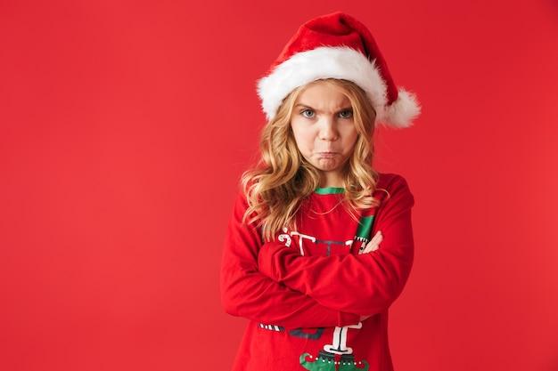 Verärgertes kleines mädchen, das weihnachtskostüm trägt, isoliert steht und schaut