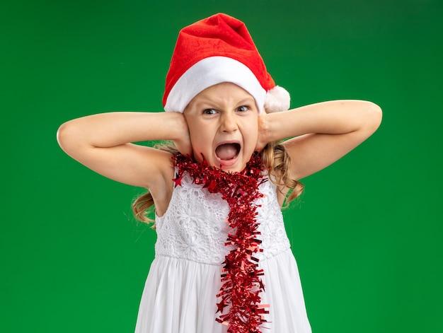 Verärgertes kleines mädchen, das weihnachtsmütze mit girlande auf halsbedeckten ohren trägt, lokalisiert auf grünem hintergrund
