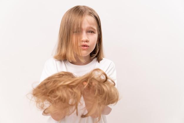 Verärgertes kleines mädchen hält in den händen abgeschnittenes haar nach dem schneiden auf weißem hintergrund. bedeutet, kinderhaare zu pflegen. schönheitssalon für kinder.