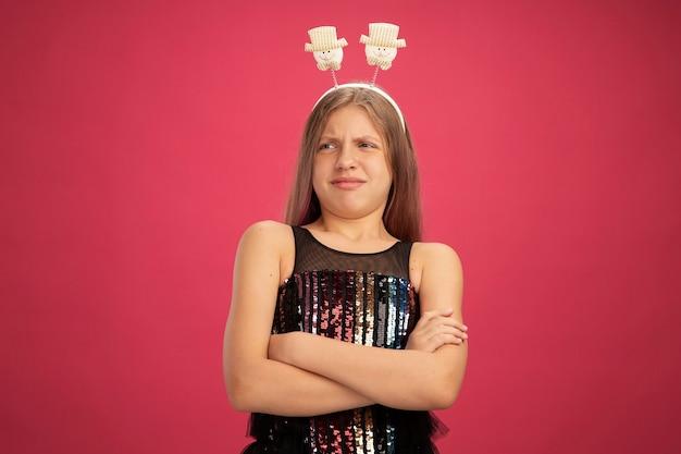 Verärgertes kleines mädchen in glitzer-partykleid und lustigem stirnband, das mit verschränkten armen das neujahrsfeier-feiertagskonzept auf rosafarbenem hintergrund beiseite schaut