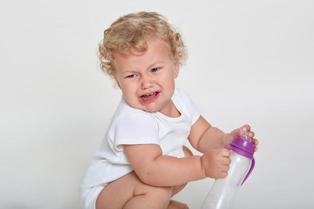 Verärgertes kleinkind weint, während es gegen den weißen raum hockt, das kind trinken will, hält eine leere trinkschale
