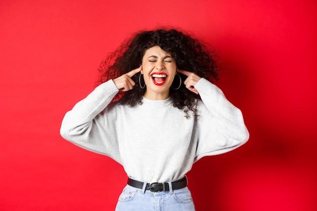 Verärgertes lockiges mädchen blockiert ohren mit fingern und schreien, gestört durch schrecklich laute geräusche, die auf rotem hintergrund stehen