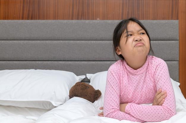 Verärgertes mädchen, das auf bett und empfindlich im schlafzimmer sitzt, verärgertes und genervtes gefühlskonzept