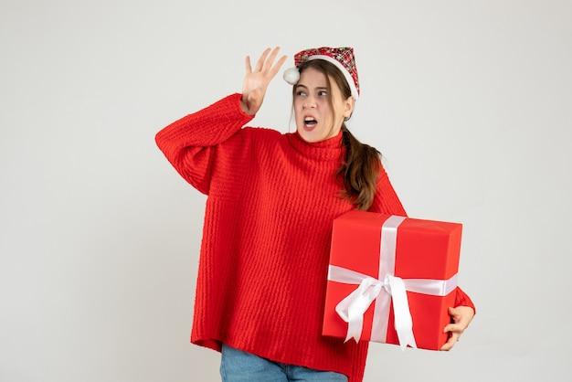 Verärgertes mädchen der vorderansicht mit der weihnachtsmütze, die das stehende geschenk hält