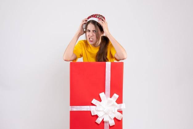 Verärgertes mädchen der vorderansicht mit weihnachtsmütze, die hinter großem weihnachtsgeschenk steht