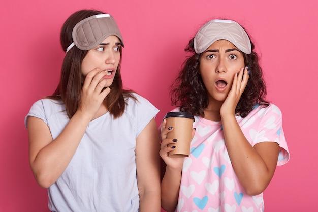 Verärgertes mädchen mit einer pappbecher kaffee, die ihre wange mit der handfläche bedeckt und in der nähe ihrer freundin mit weit geöffnetem mund posiert