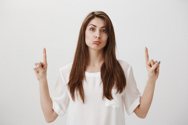 Verärgertes niedliches schmollendes mädchen, das finger nach oben zeigt