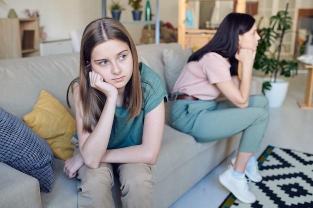 Verärgertes oder beleidigtes teenager-mädchen mit ihrer hand an der wange, das während eines konflikts mit ihrer gelangweilten oder verärgerten mutter auf der couch sitzt