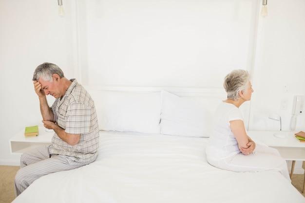 Verärgertes paar, das im schlafzimmer sich ignoriert