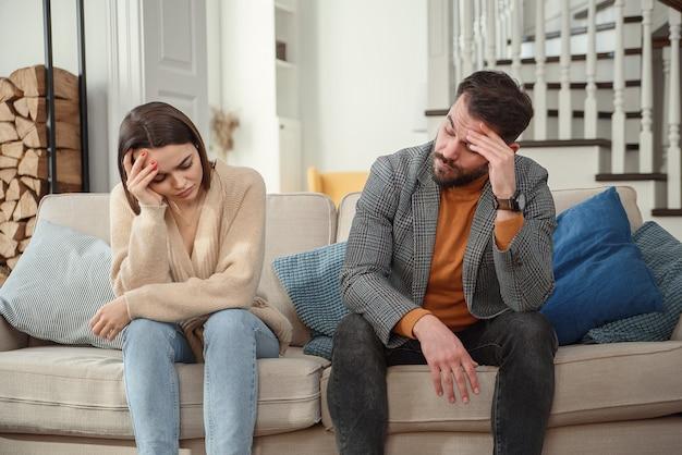Verärgertes paar zu hause. hübscher mann und schöne junge frau haben streit. zusammen auf dem sofa sitzen. familienprobleme.