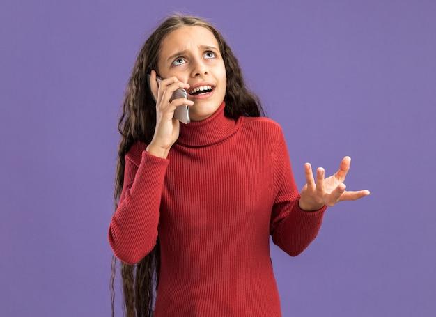 Verärgertes teenager-mädchen, das am telefon spricht und nach oben schaut und leere hand zeigt, die auf purpurroter wand isoliert ist?