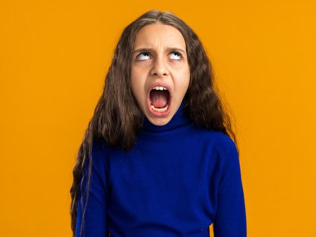 Verärgertes teenager-mädchen, das schreiend auf orangefarbener wand isoliert aufschaut?