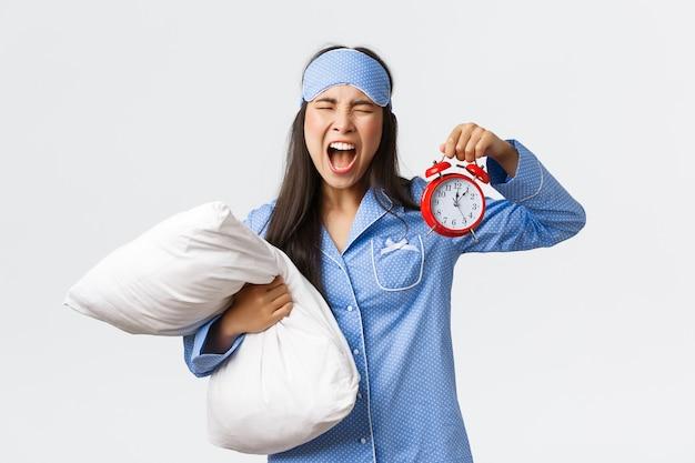 Verärgertes und verrücktes asiatisches mädchen in blauen pyjamas und schlafmaske, das frustriert schreit, als verschlafen, wecker zeigt und belästigt schreit, zu spät zur arbeit kommt, kissen hält.