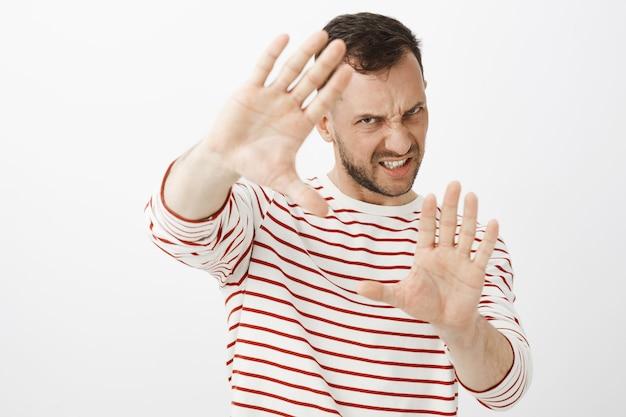Verärgertes wütendes männliches model mit borsten, die handflächen in richtung ziehen, um sich vor angriffen zu schützen oder zu verteidigen