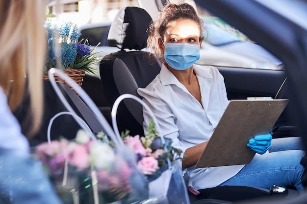 Verantwortliche floristin, die eine blumenlieferung mit dem auto durchführt